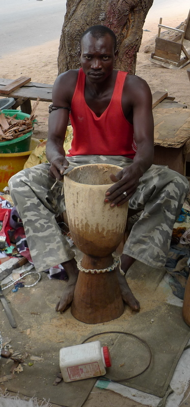 Whittling drums to sell at Bakau Market